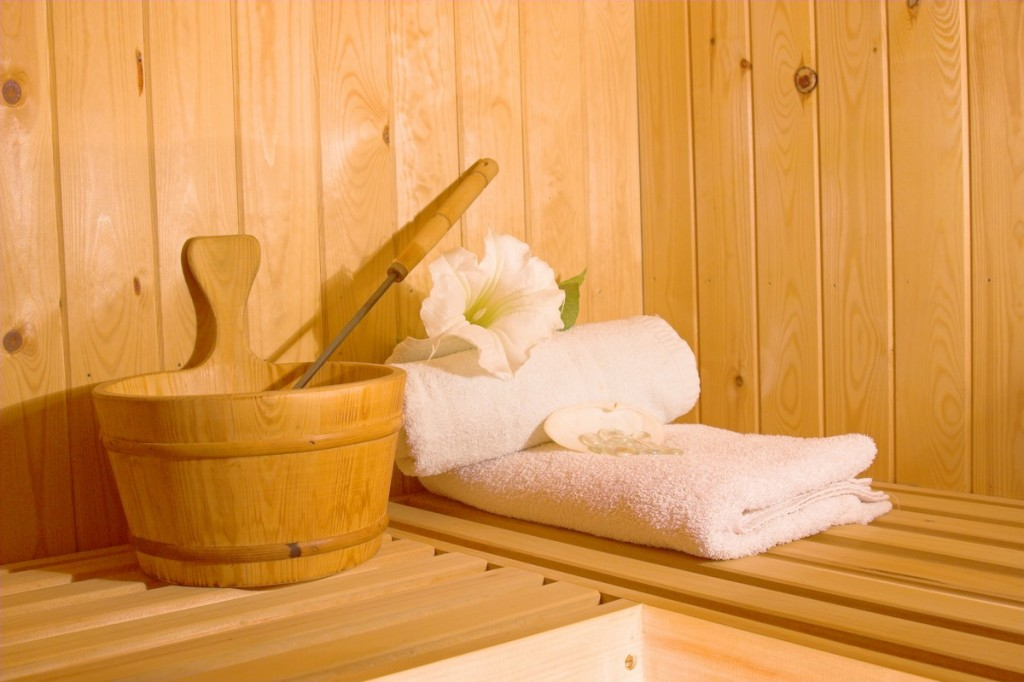 Sauna with towels, bucket and ladle and tropical flower just waiting for occupant